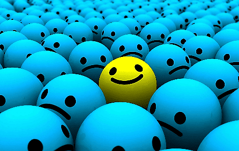 Yellow smiley face in the midst of frowing blue faces