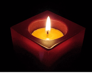 Candle burning brightly in a red container